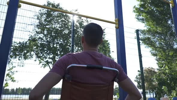 Thumbnail for Young Disabled Man in Wheelchair Engaged on the Crossbar Outdoors