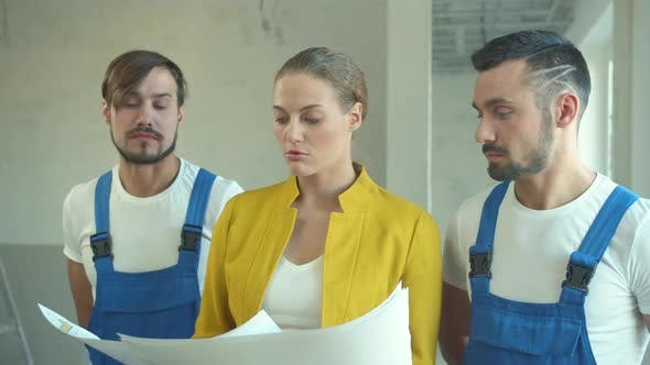 Woman Explains and Shows To Repairmen a Work Plan
