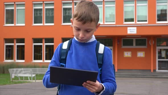 Thumbnail for A Young Boy Works on a Tablet in Front of an Elementary School