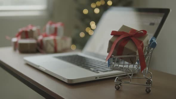 Gift Box In Cart With Blurred A Laptop On Desk At Home In Christmas Time