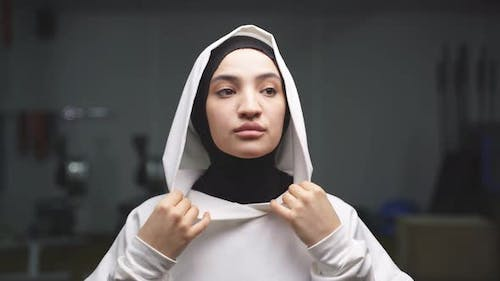 Muslim Woman Puts on a Hood From a Sports Hijab for a Workout in the Gym of a Fitness Center
