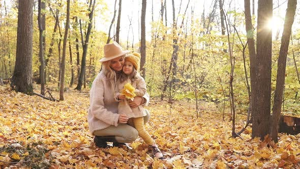 Blonde Adult Woman with Daughter in Autumn Forest