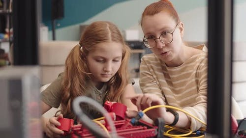 Female Teacher and Intelligent Teenage Girl Conducting Tech Project