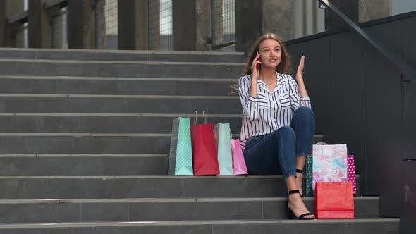 Thumbnail for Girl Sitting on Stairs with Bags Talking on Mobile Phone About Sale in Shopping Mall in Black Friday