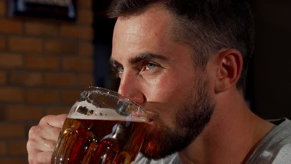 Thumbnail for Handsome Bearded Man Smiling Joyfully While Drinking Beer