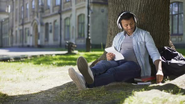 Thumbnail for Mixed-Race Guy Sitting Under Tree in Headphones Writing in Notebook Song Writer