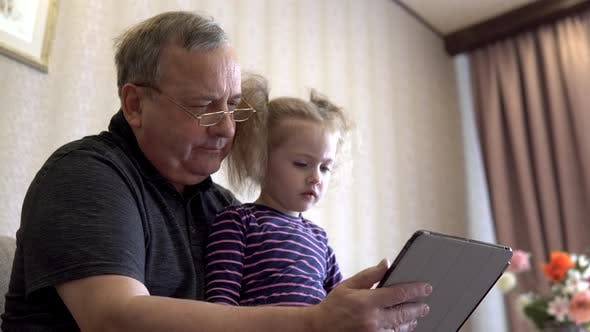 Thumbnail for Granddaughter and Grandfather Are Sitting with a Tablet. The Girl Frowns at the Tablet. Sitting on