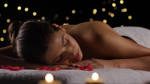 Thumbnail for Girl Sleeps After Spa Treatments on Rose Petals, Burning Candles