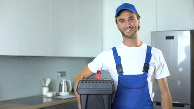 Handyman Holding Tools Standing in Kitchen, Professional Plumbing Services