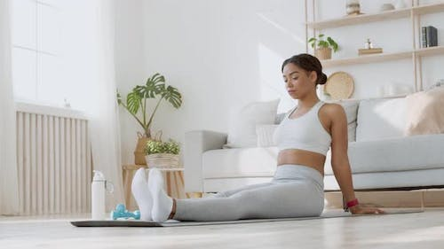 Young African American Lady Warming Up Her Feet, Rotating Ankles, Sitting on Exercise Mat on Floor