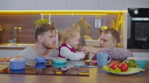 Gay Parents and Child Enjoying Leisure at Home