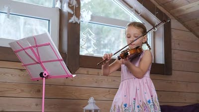 Cute Little Violinist Exercising in the Attic