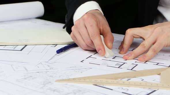 Thumbnail for Builder Sits at the Table and Analyzes the Drawing of the New Store. Close Up
