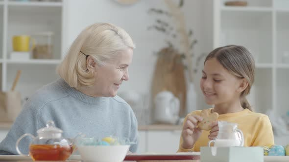 Thumbnail for Happy Girl and Grandmother Enjoying Easter Cookies