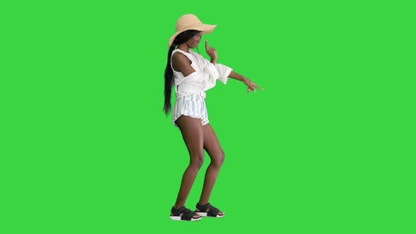 Thumbnail for Cheerful African American Girl in a Straw Hat Dancing on a Green Screen, Chroma Key.