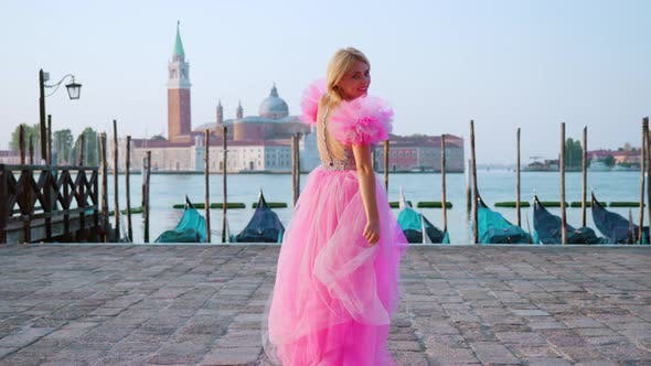 Woman with Beautiful Pink Dress Walks in Front of the Gondolas in Venice