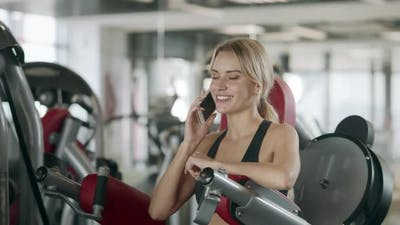 Beautiful Woman Using Mobile Phone After Fitness Training