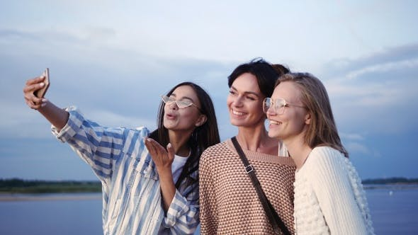 Thumbnail for Group of happy female friends laughing and taking a selfie