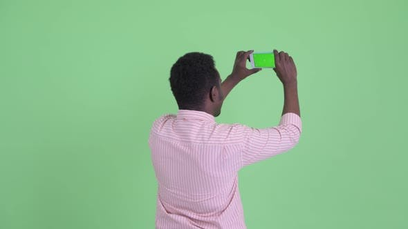 Thumbnail for Rear View of Young African Businessman Taking Picture with Phone