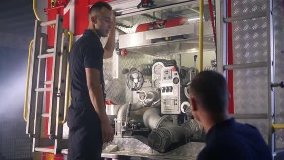 Fireman Teaching Trainee To Use Fire Engine Equipment
