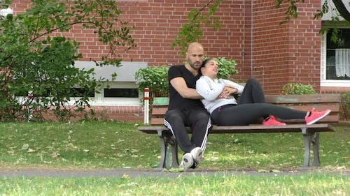Young Loving Couple Is Sitting On Bench