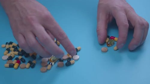 Man Hand with Pills, Tablets, Vitamins, Drugs, Capsules Isolated on Blue Background. Coronavirus