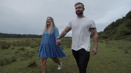 Blonde Woman and Buffed Man Walking Hand in Hand