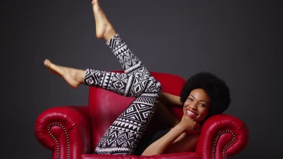 Thumbnail for Black woman in red leather arm chair kicking legs playfully