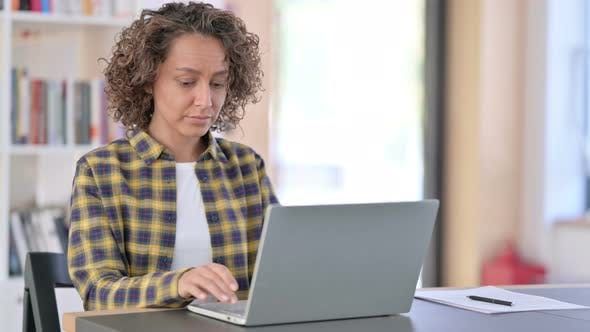 Excited Mixed Race Woman Celebrating Success on Laptop
