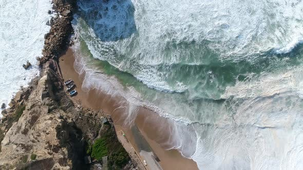 Aerial View of Foaming Waves Around a Cliff