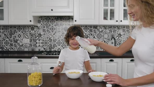 Thumbnail for Woman in White Dress Pouring the Milk Into Bowl with Corn Flakes while Her Smiling Son