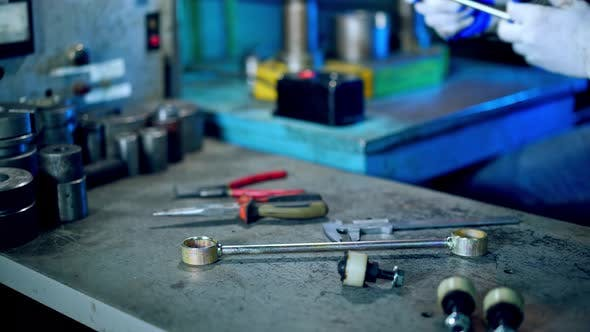 Metal Formation by Hydraulic Press. Worker at manufacture workshop operating metal press machine