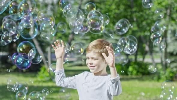 Thumbnail for Happy Blonde Boy Enjoying Soap Bubbles