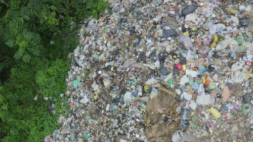 Top down view of a garbage landfill, showing the loads of garbage being dumped