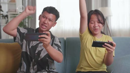 Asian Children Playing Video Games On Mobile Phone And Celebrating Victory At Home