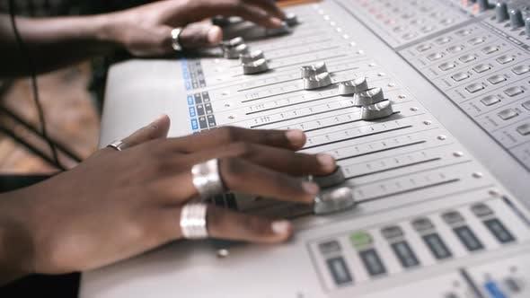 Hands of Audio Engineer Mixing Music