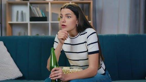 Femme assise sur le canapé devant la télévision pendant la compétition sportive