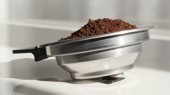 Ground coffee in espresso machine holder 4K footage