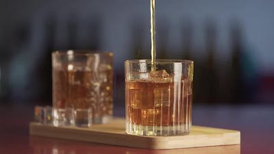 Whiskey poured in glass from bottle. Close-up of glass of whisky with ice cubes
