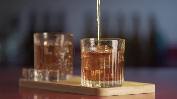 Thumbnail for Whiskey poured in glass from bottle. Close-up of glass of whisky with ice cubes