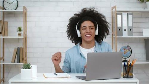 Cheerful Guy Wearing Headphones Dancing Listening Music At Laptop Indoors