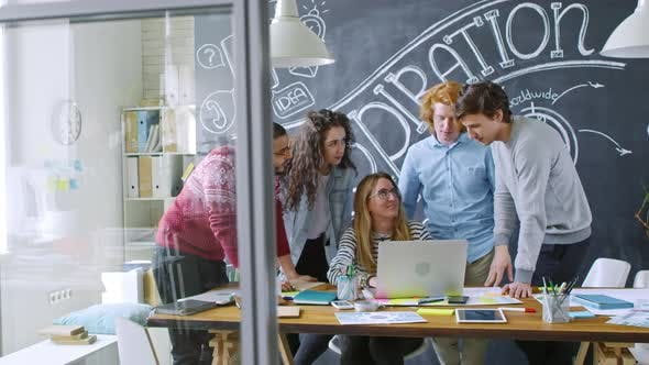 Cover Image for Group of Young Coworkers Discussing Project on Laptop in Creative Office