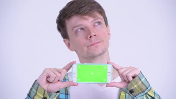 Thumbnail for Face of Happy Young Handsome Man Thinking While Showing Phone