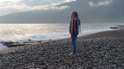 Little Girl Enjoy Watching the Sea View at Sunset