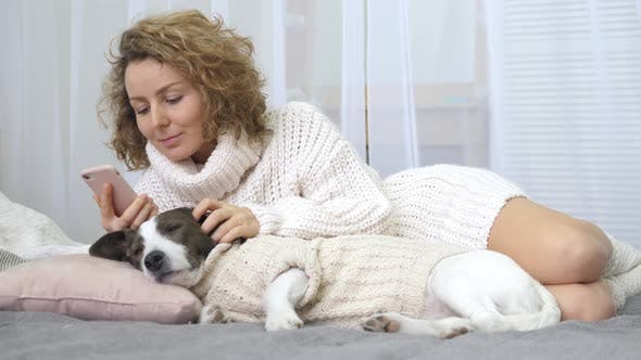 Thumbnail for Young Woman Using Cell Phone Lying In Bed With Dog At Cozy Home