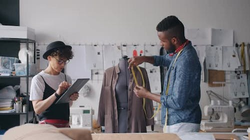 Creative Designers Measuring Garment and Using Tablet Working in Studio Together