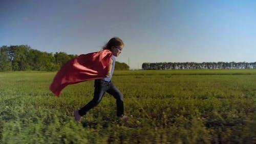 Kleines Mädchen-Kind auf einem Feld in einem Superhelden-Kostüm