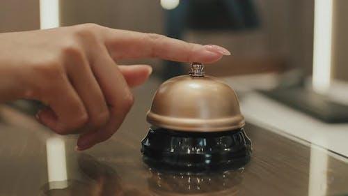 Hand Ringing Service Bell on Hotel Reception Desk