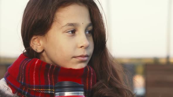 Thumbnail for A Thoughtful Girl Drinks a Warm Drink From a Hot Becher