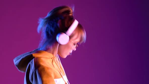 Teen Girl Wear Kopfhörer Musik hören auf lila Neon-Studio-Hintergrund